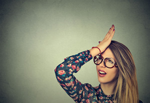Regrets wrong doing. Closeup portrait silly young woman, slapping hand on head having duh moment isolated on gray background. Negative human emotion facial expression feeling, body language, reaction